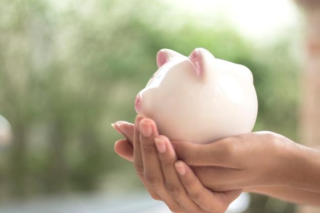 Mão de mulher segurando o espaço vazio de mealheiro espaço vazio Foto Premium