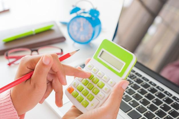 Mão de mulher segurando o lápis vermelho e trabalhando com calculadora Foto Premium