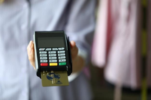 Mão de mulher segurar pos termimal com cartão de débito plástico ouro Foto Premium