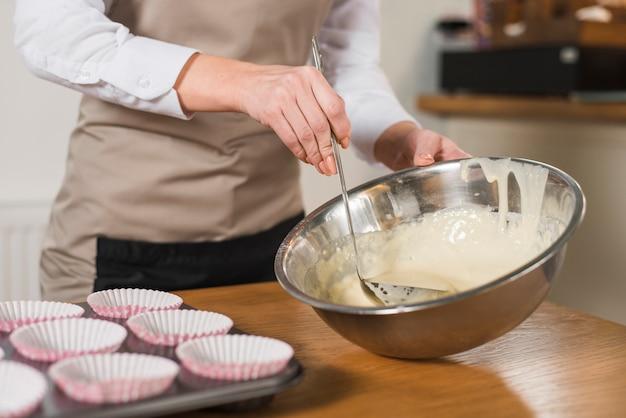 Mão de mulher tomando bolo misturar com concha da tigela de aço inoxidável Foto gratuita