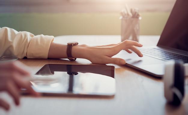 Mão de mulher trabalhando no tablet e pressione o laptop em cima da mesa no escritório. Foto Premium