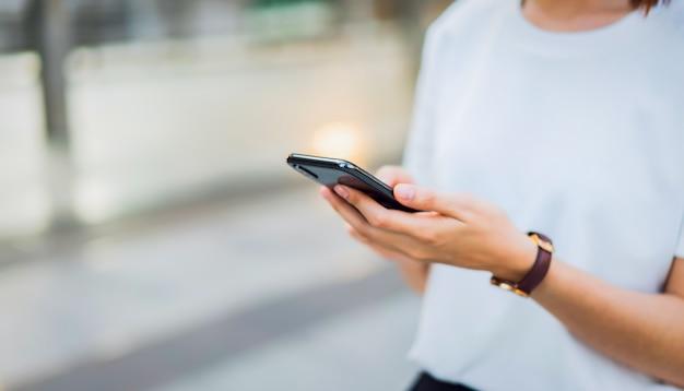 Mão de mulher usando smartphone preto. o conceito de usar o telefone é essencial na vida cotidiana. Foto Premium