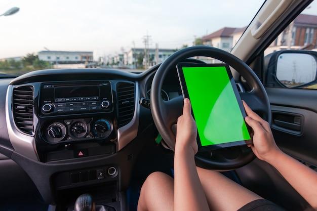 Mão de mulher usando tablet com monitor de tela verde em branco no carro suv Foto Premium