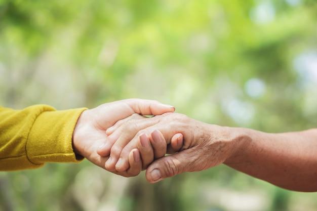 Mão de mulher velha e ong segurando um ao outro Foto Premium
