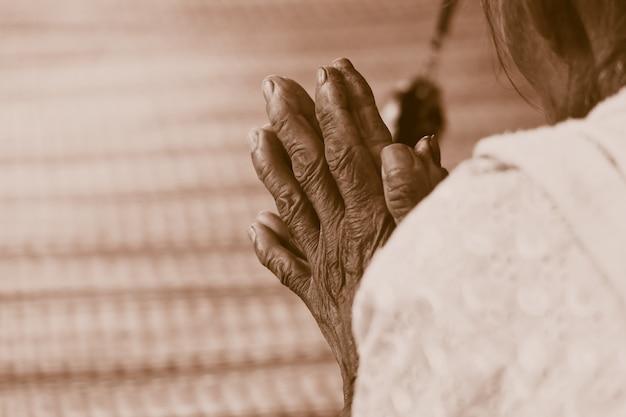 Mão de mulher velha, rezando o tom retrô vintage Foto Premium