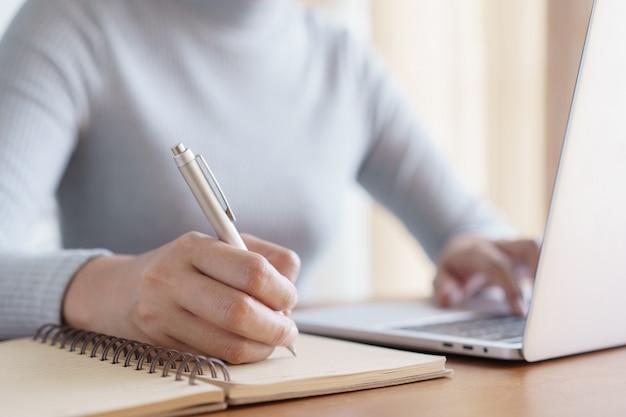 Mão de mulheres de negócios usando o laptop e escrever o caderno enquanto está sentado trabalhando sobre a mesa no escritório Foto Premium