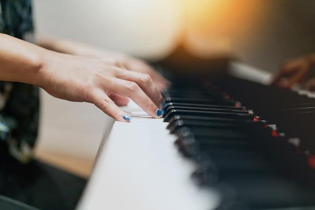 Mão de mulheres no clássico teclado de piano closeup Foto Premium