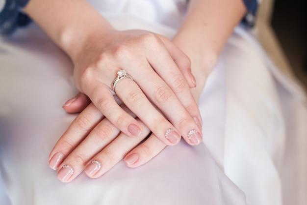 Mão de noiva com manicure no vestido de casamento Foto Premium