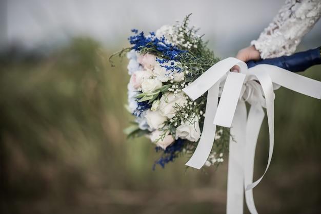 Mão de noiva segurando flor no dia do casamento Foto gratuita