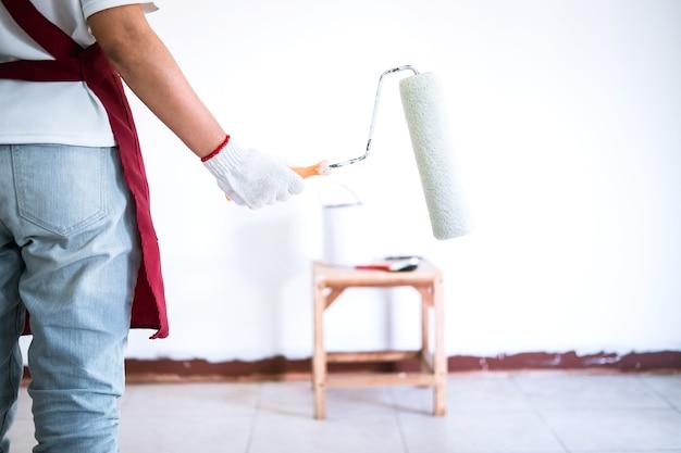 Mão de pintor na parede de pintura de luva branca com rolo de pintura na sala, forma e estrutura Foto Premium