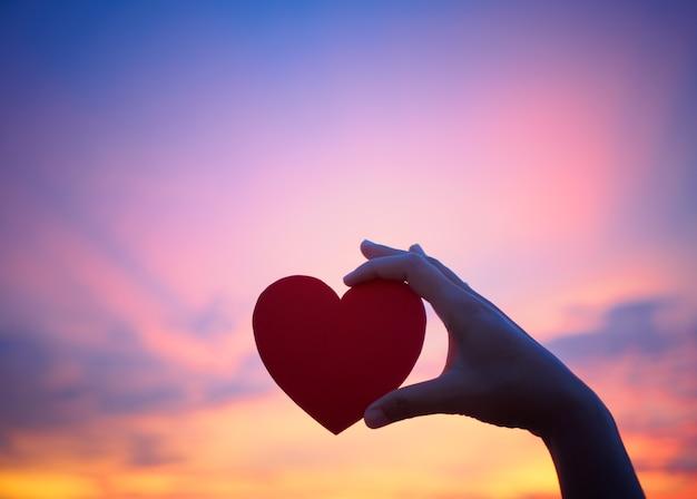 Mão de silhueta segurando coração lindo durante o fundo por do sol Foto Premium