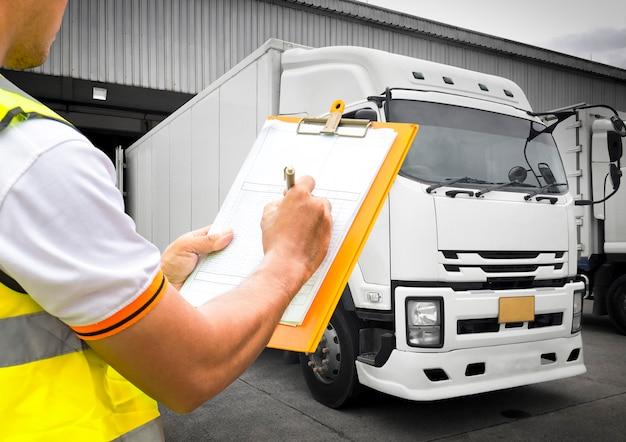 Mão de trabalhador de armazém segurando a área de transferência inspecionando carregar o controle de remessa com caminhões, transporte de logística da indústria de frete Foto Premium