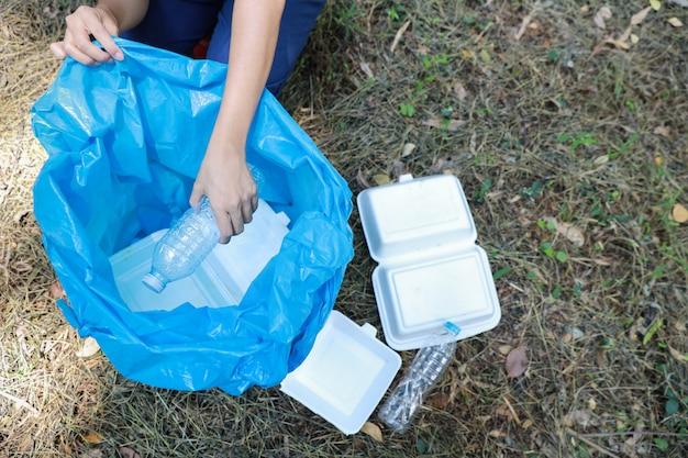Mão de turista voluntário limpar o lixo e restos de plástico na floresta suja em grande saco azul Foto Premium