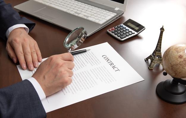 Mão de um empresário, olhando para um documento de contrato através de uma lupa. Foto Premium