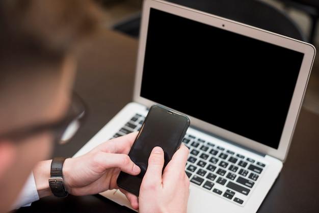 Mão de um homem de negócios usando o celular na frente do laptop Foto gratuita