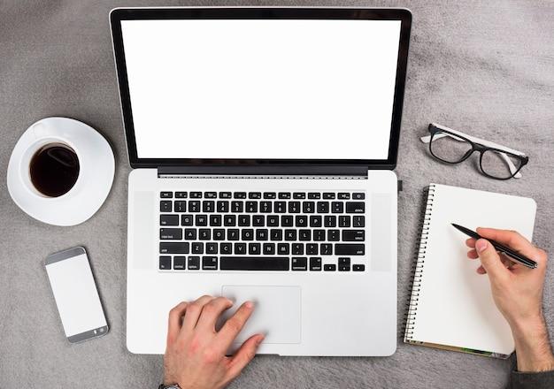 Mão de um homem de negócios usando tablet digital escrevendo no bloco de notas em espiral sobre a mesa cinza Foto gratuita