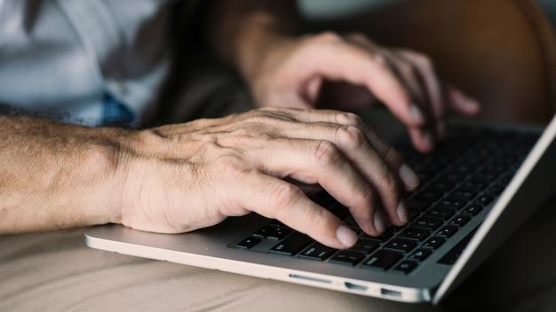 Mão de um homem idoso digitando no laptop Foto gratuita