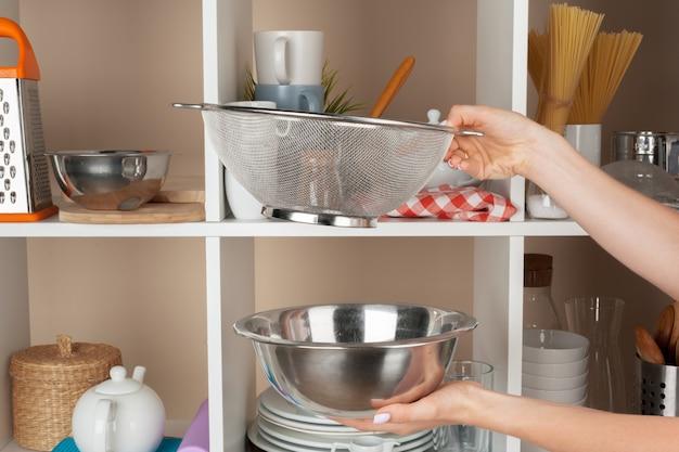 Mão, de, um, mulher, levando, kitchenware, de, um, cozinha, prateleira Foto Premium