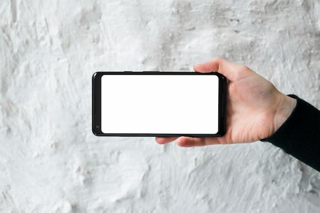 Mão, de, um, pessoa, mostrando, tela móvel telefone, contra, branca, parede concreta Foto gratuita