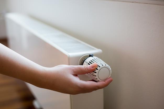 Mão de uma jovem alterando a temperatura no radiador pelo controlador de temperatura Foto Premium