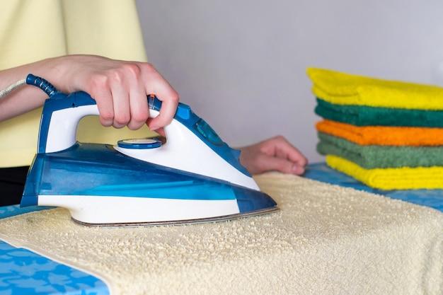 Mão de uma mulher acariciando uma almofada de toalhas na tábua de passar Foto Premium