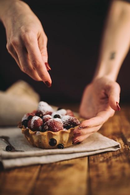 Mão de uma mulher, adicionando os mirtilos sobre a torta de frutas na mesa de madeira Foto gratuita