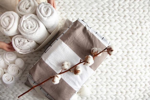 Mão de uma mulher bem cuidada segurando um galho de algodão com uma pilha de lençóis cuidadosamente dobrados perto de toalhas enroladas em uma cesta de malha colocada em uma manta de lã de merino grossa de malha. têxtil natural. vista do topo. Foto Premium