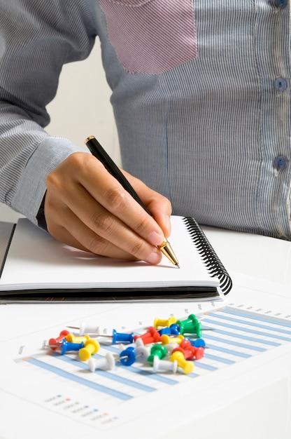 Mão de uma mulher escrevendo com caneta na agenda Foto Premium