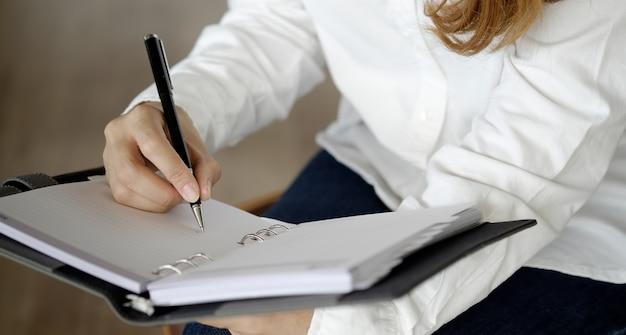 Mão de uma mulher escrevendo no caderno em branco na mesa Foto Premium