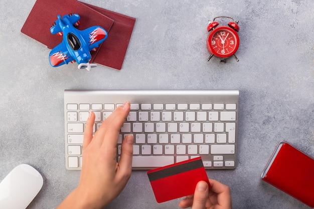 Mão de uma mulher está digitando o teclado e leve o cartão de crédito perto de passaporte e relógio de avião pequeno Foto Premium