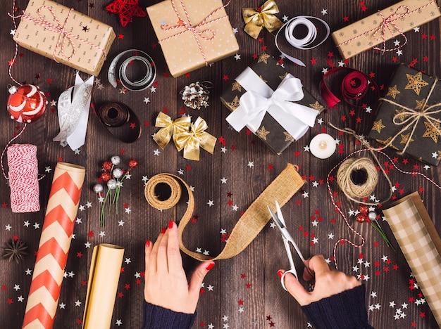 Mão de uma mulher segurando a fita de serapilheira com uma tesoura para cortar e embalar a caixa de presente de natal Foto gratuita