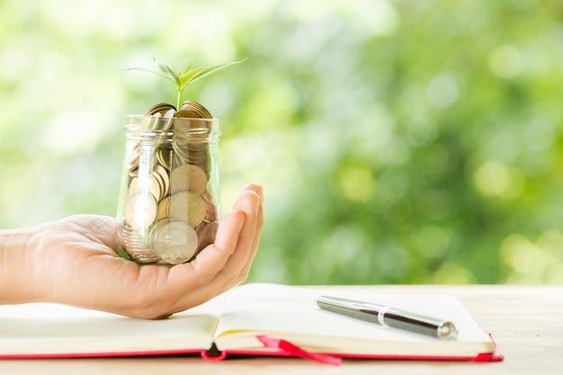 Mão de uma mulher segurando a planta que cresce da garrafa de moedas Foto gratuita