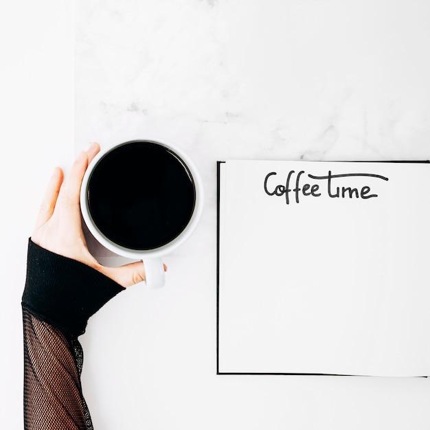 Mão de uma mulher segurando a xícara de café com texto manuscrito no caderno sobre a mesa Foto gratuita