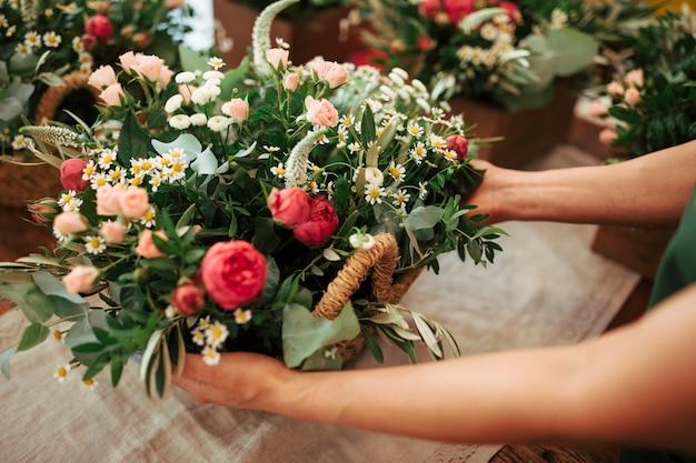 Mão de uma mulher segurando cesta pf flores frescas Foto gratuita