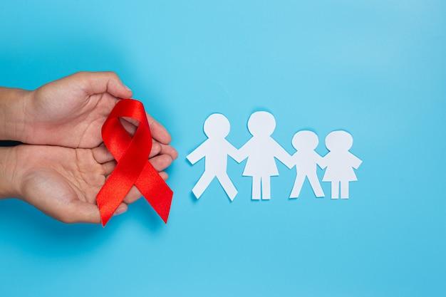 Mão de uma mulher segurando o conceito de conscientização de hiv fita vermelha dia mundial da aids e dia mundial da saúde sexual. Foto gratuita
