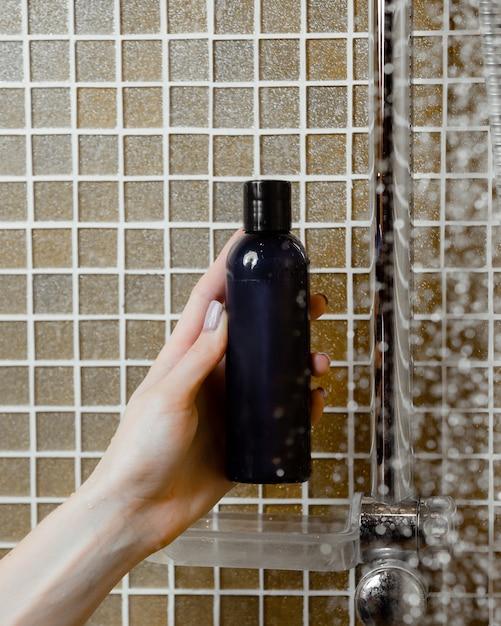 Mão de uma mulher segurando o gel de banho na garrafa da marinha no banheiro Foto gratuita