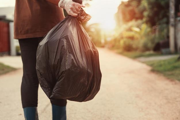 Mão de uma mulher segurando o saco de lixo para reciclar colocando no lixo Foto Premium