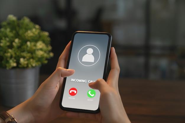Mão de uma mulher segurando o telefone e mostrar a chamada de tela. Foto Premium