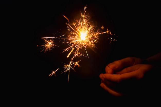 Mão de uma mulher segurando um diamante ardente Foto Premium