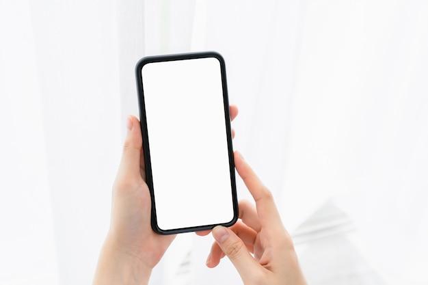 Mão de uma mulher segurando um smartphone e a tela está em branco, conceito de rede social Foto Premium