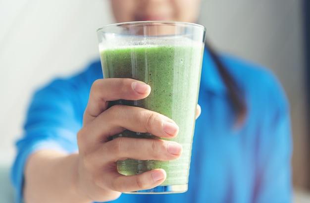 Mão de uma mulher segurando um suco de suco de vegetais Foto Premium