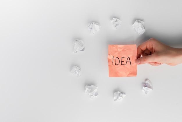 Mão de uma mulher segurando uma nota auto-adesiva com texto de idéia, rodeado por papel amassado branco Foto gratuita