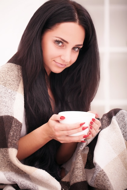 Mão de uma mulher segurando uma xícara de café. com uma linda manicure de inverno. bebida, moda, manhã Foto Premium