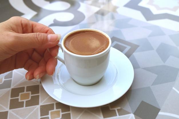 Mão de uma mulher segurando uma xícara de café turco, servido em uma mesa mourisca Foto Premium
