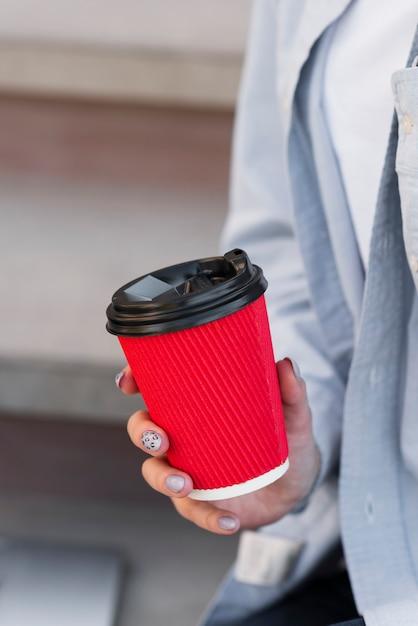 Mão de uma mulher segurando uma xícara de café Foto gratuita