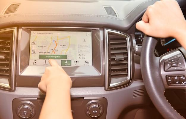 Mão de uma mulher tocando o sistema multimídia de tela com o aplicativo de navegação gps. Foto Premium