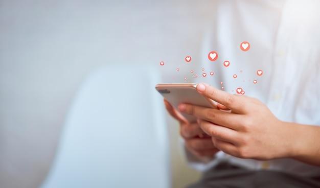 Mão de uma mulher usando o smartphone e mostrar mídia social de ícone de coração. rede social de conceito. Foto Premium