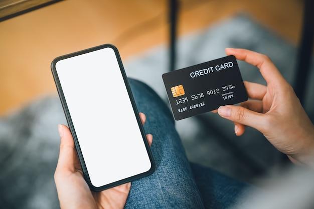 Mão de uma mulher usando smartphone e segurando o cartão de crédito com pagamento online no celular. Foto Premium