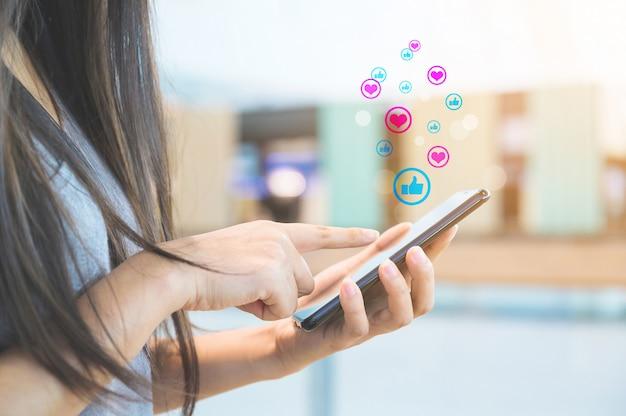 Mão de uma mulher usando smartphone móvel com mídia social ícone e rede social. conceito de marketing on-line Foto Premium