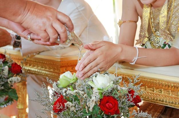 Mão de uma noiva, recebendo água benta de anciãos na cerimônia de casamento de cultura tailandesa Foto Premium